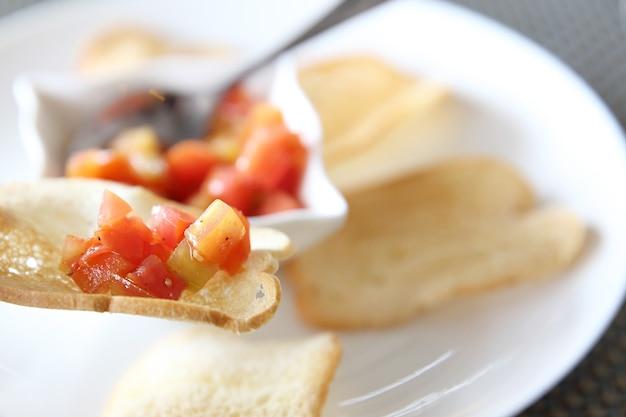 Comida italiana de aperitivos, fatias de bruschetta de baguete torrada guarnecida com manjericão e tomate