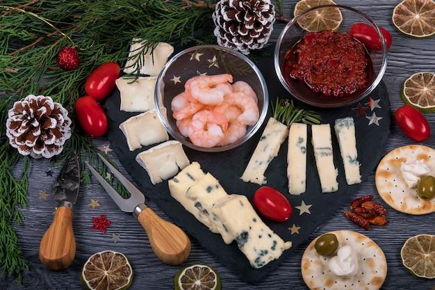 Comida italiana em uma bandeja de queijo escuro com decoração de natal.