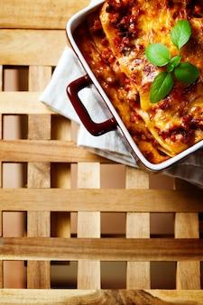 Comida italiana. placa de lasanha na mesa de madeira.