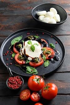 Comida italiana - salada caprese com tomate fatiado, queijo mussarela, manjericão. servido em chapa preta sobre fundo escuro de madeira. vista do topo. vertical.