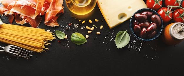 Comida italiana tradicional com espaguete, tomate, queijo, azeitonas e azeite no escuro