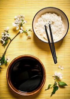 Comida japonesa arroz cozido com molho de soja e os ramos de cereja