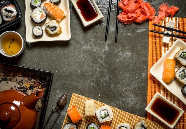 Comida japonesa. chá perfumado, sushi e pãezinhos com gengibre em conserva e molho de soja.