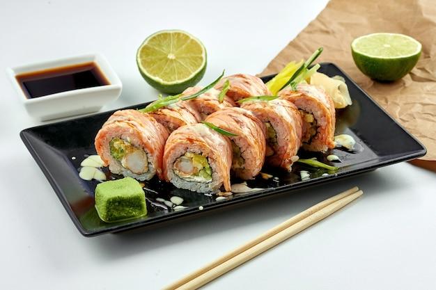 Comida japonesa clássica - rolinho de sushi da filadélfia com salmão assado, molho picante, cream cheese, tempura de camarão e pepino servido em um prato preto sobre um prato branco.