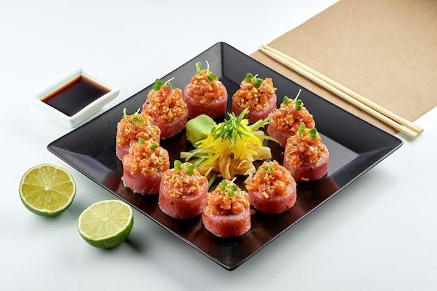 Comida japonesa clássica - rolo de sushi da filadélfia com salmão picante e atum servido em uma placa preta em uma placa branca. close up, foco seletivo