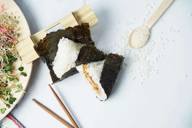 Comida japonesa feita de arroz branco transformado em triangular com camarão frito. copie o espaço