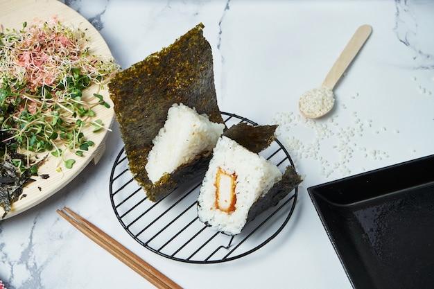 Comida japonesa feita de arroz branco transformado em triangular com carne de porco frita. copie o espaço