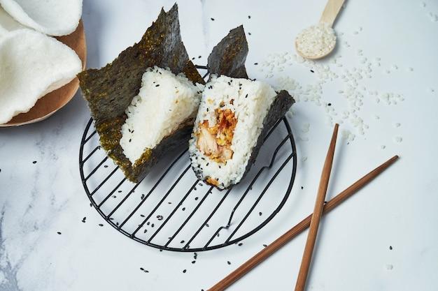 Comida japonesa feita de arroz branco transformado em triangular com frango frito pan. copie o espaço