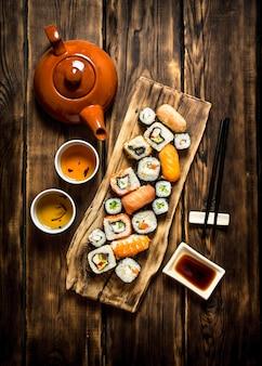 Comida japonesa. os rolos de sushi e o chá de ervas.