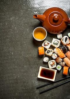 Comida japonesa os rolos e sushi com molho de soja e chá de ervas