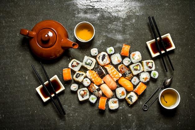 Comida japonesa. os rolos e sushi com molho de soja e chá de ervas.