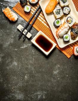 Comida japonesa. os rolos e sushi com molho de soja no carrinho de bambu.