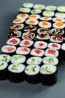 Comida japonesa. rolinhos com abacate maduro, peixe vermelho, salmão, arroz fresco com legumes em nori. conjunto com rolos