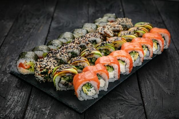 Comida japonesa rolls com atum de salmão em mesa preta