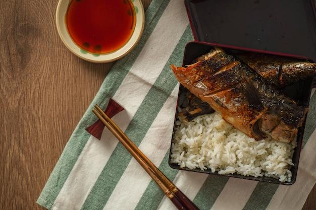 Comida japonesa, saba grelhado ou cavala com molho doce, servido com arroz cozido, colocado sobre a mesa de madeira