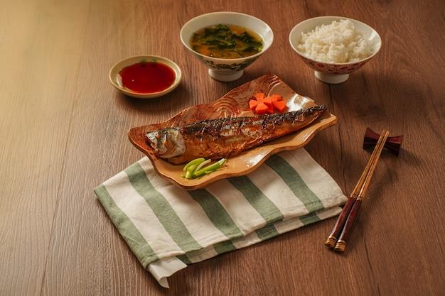 Comida japonesa, saba grelhado ou cavala com molho doce, servido com sopa de missô e arroz cozido, colocado na mesa de madeira