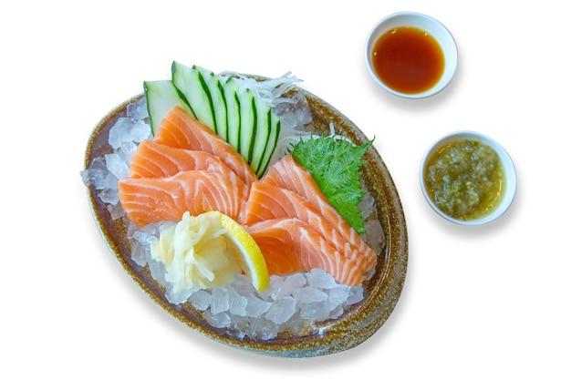 Comida japonesa, salmão fresco em uma tigela no gelo com molho de frutos do mar e pepino em fatias, foco seletivo.