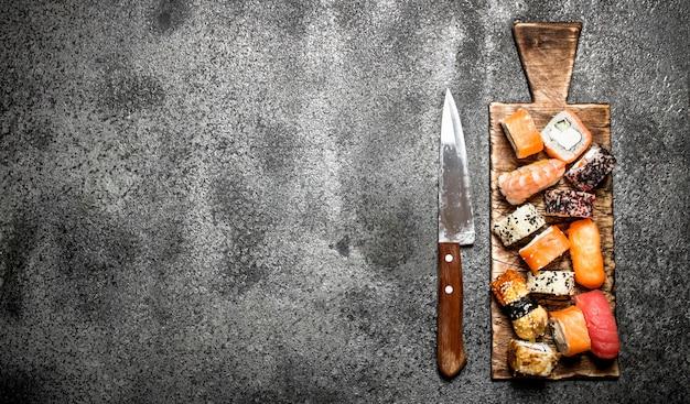 Comida japonesa sushi fresco e pãezinhos em fundo rústico