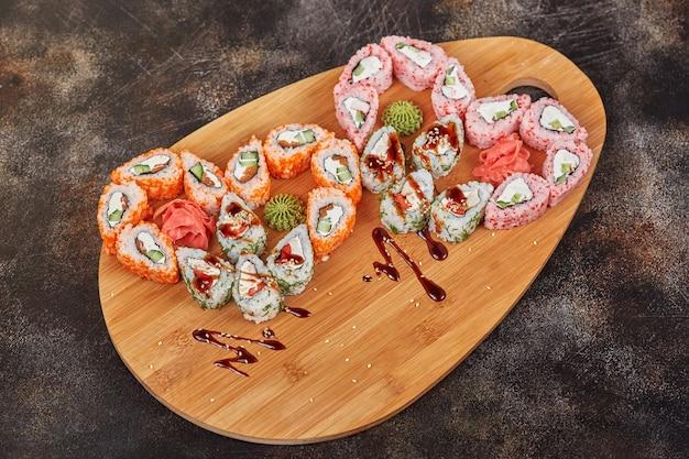 Comida japonesa sushi maki rola na placa de madeira, em forma de coração