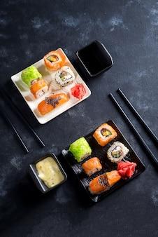Comida japonesa-sushi, rolos, pauzinhos, molho de soja no fundo preto ardósia