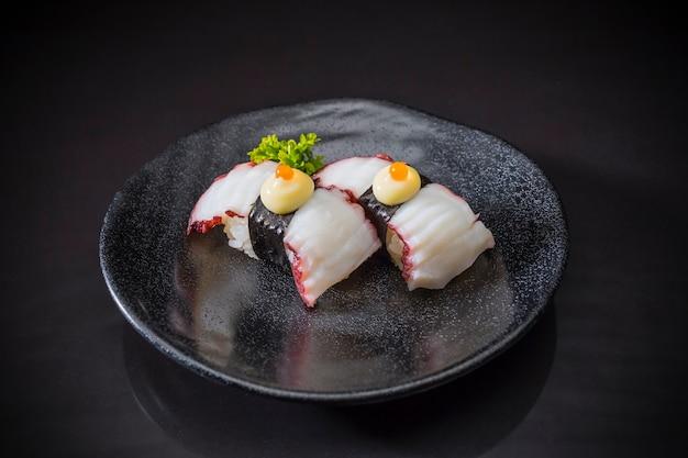 Comida japonesa, tako nigiri sushi servido em prato de cerâmico, sushi nigiri em fundo preto