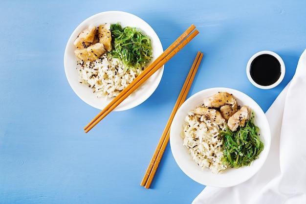 Comida japonesa tigela de arroz, peixe branco cozido e wakame chuka ou salada de algas. vista do topo. configuração plana
