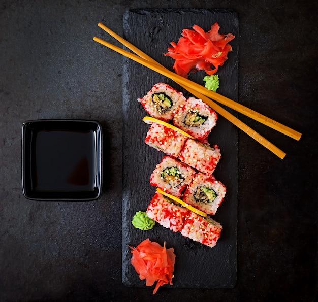 Comida japonesa tradicional - sushi, pãezinhos e molho em um fundo preto. vista do topo