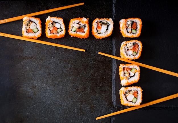 Comida japonesa tradicional - sushi, pãezinhos e pauzinhos para sushi em um fundo escuro. vista do topo