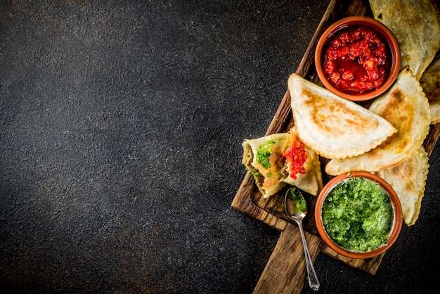 Comida latino-americana, mexicana e chilena. empanadas de massa assada tradicional com carne de bovino, dois molhos picantes