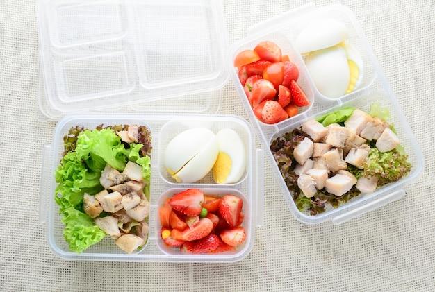 Comida limpa estilo moderno, ovo cozido, frango grelhado e abacate, morango, salada de legumes