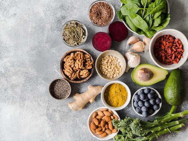 Comida limpa saudável - legumes, frutas, nozes, superalimentos em um fundo cinza.