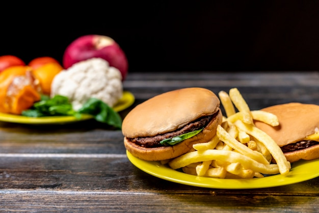 Comida lixo ou vegetais e frutas saudáveis na mesa de madeira escura isolada b