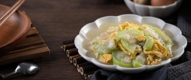 Comida local caseira taiwanesa de ovos mexidos com bucha e óleo de gergelim em um prato no fundo da mesa rústica.