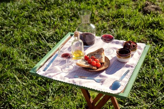 Comida mediterrânea com azeite e vinho tinto piquenique no jardim ao pôr do sol