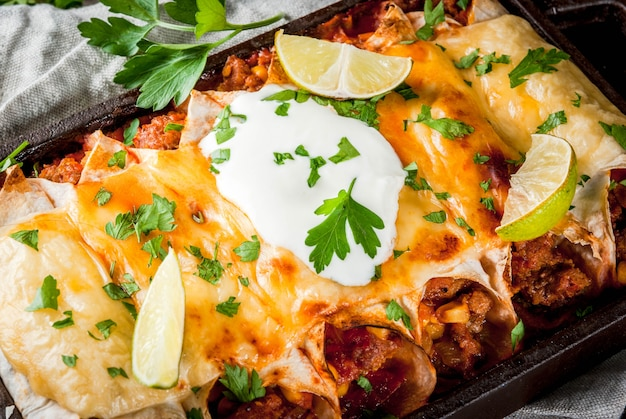 Comida mexicana. culinária da américa do sul. prato tradicional de enchiladas de carne picante com milho, feijão, tomate. em uma assadeira, sobre fundo de madeira rústica velha. fechar vista