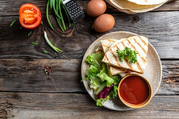 Comida mexicana culinária tradicional prato de quesadilla com ovos mexidos, vegetais, presunto e queijo