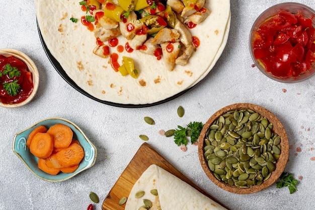 Comida mexicana e burrito perto de vegetais e sementes de cardamomo