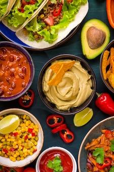 Comida mexicana mista. comida de festa. guacamole, nachos, fajita, tacos de carne, salsa, pimentão, tomate em uma mesa de madeira. vista do topo.