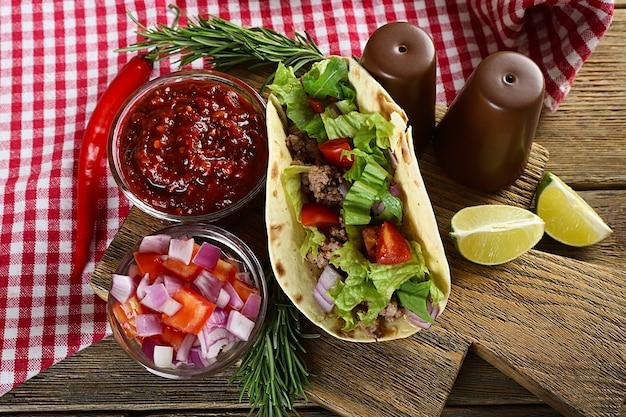 Comida mexicana taco na tábua de madeira, closeup