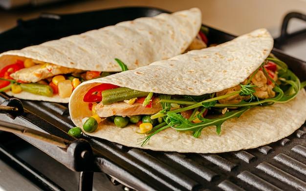 Comida mexicana tradicional. tacos com legumes e frango na panela de grelhar.