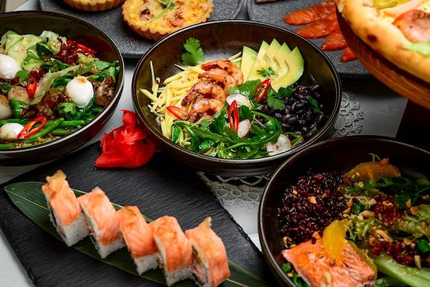 Comida mista, há pratos diferentes na mesa do restaurante, para pessoas diferentes