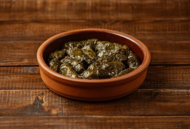 Comida nacional yarpaq dolmasi, folhas de uva com carne por dentro, cozidas dentro de uma tigela de cerâmica