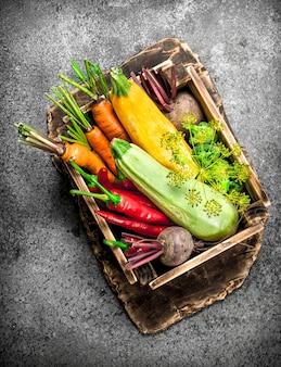 Comida orgânica. colheita de legumes em uma velha caixa sobre uma mesa rústica.