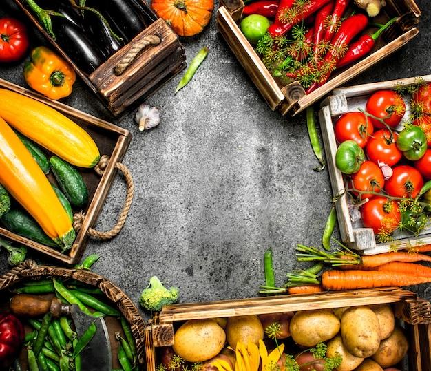 Comida orgânica. colheita fresca de vegetais em caixas sobre uma mesa rústica.