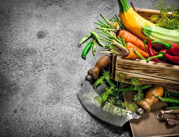 Comida orgânica. colheita fresca de vegetais em uma caixa velha. sobre um fundo rústico.
