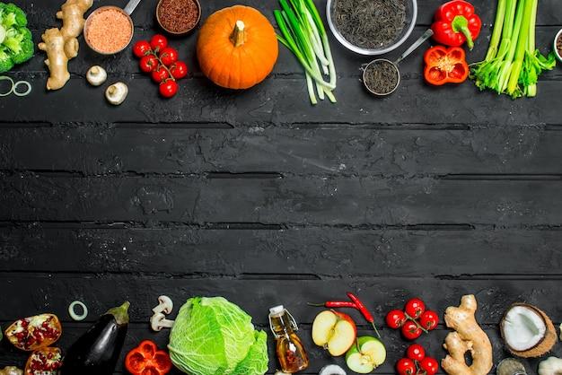 Comida orgânica. vários vegetais orgânicos e frutas na mesa de madeira preta.