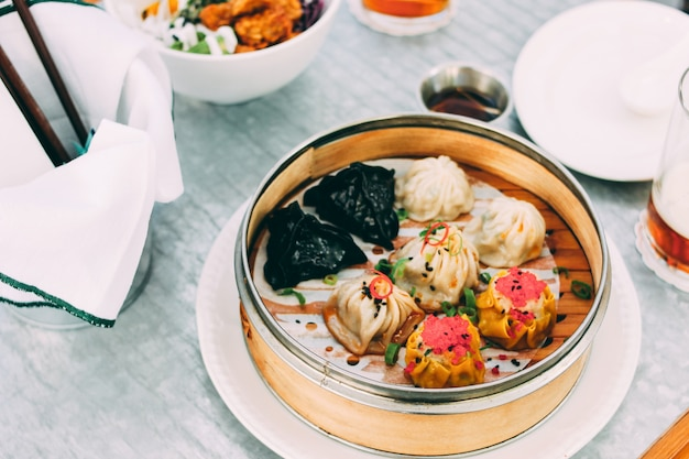 Comida pan-asiática - diferentes somas não ofuscantes em uma tigela de bambu e salada no café. almoço para dois com cerveja
