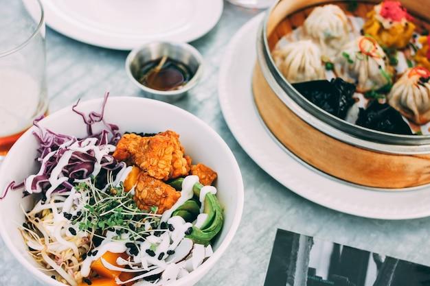 Comida pan-asiática - tigela de salada de vegetais e somas não ofuscantes diferentes no restaurante. almoço para dois com cerveja