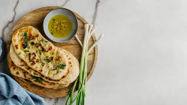 Comida paquistanesa em uma placa de madeira com cópia-espaço