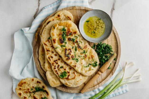 Comida paquistanesa em uma placa de madeira plana